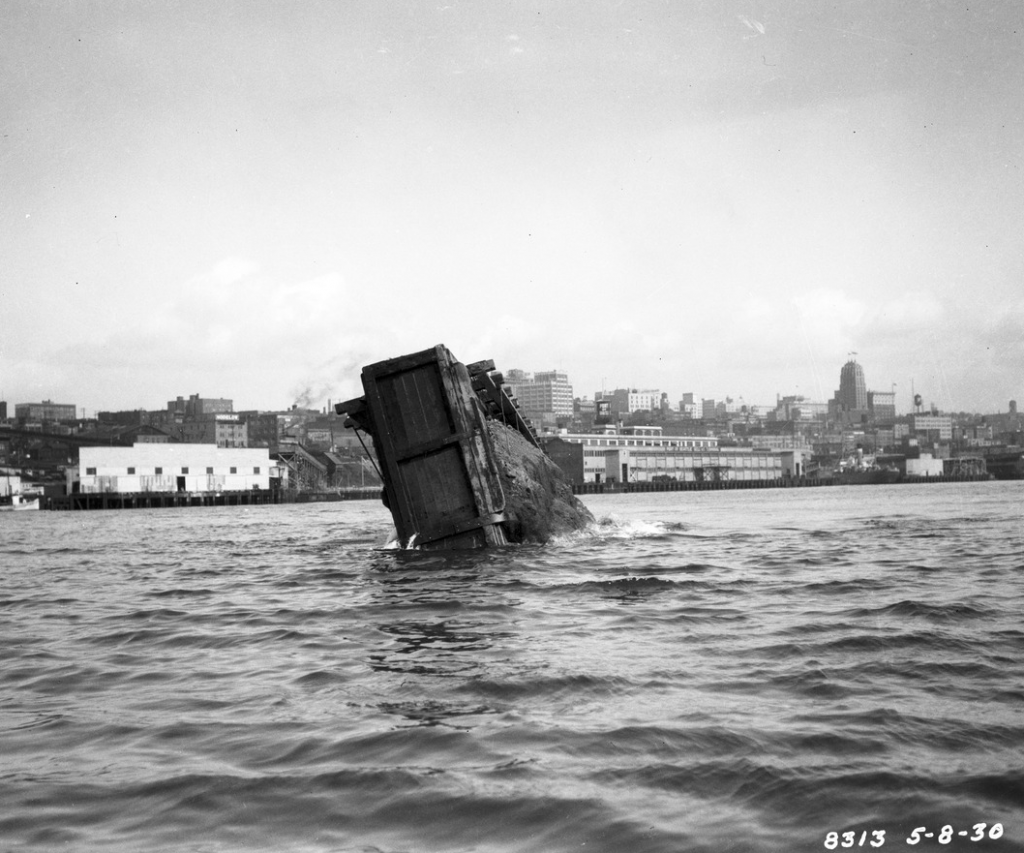 Lopsided barge dumping its load into Elliott Bay May 1930
